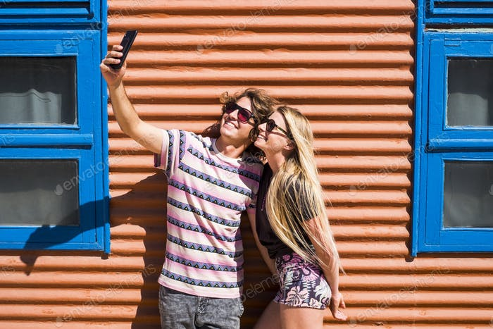 Young beautiful millennial caucasian couple of people man and woman taking selfie picture