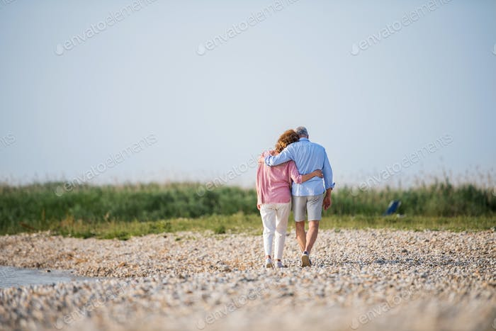 Rear view of senior couple on a holiday on a walk by the lake, walking