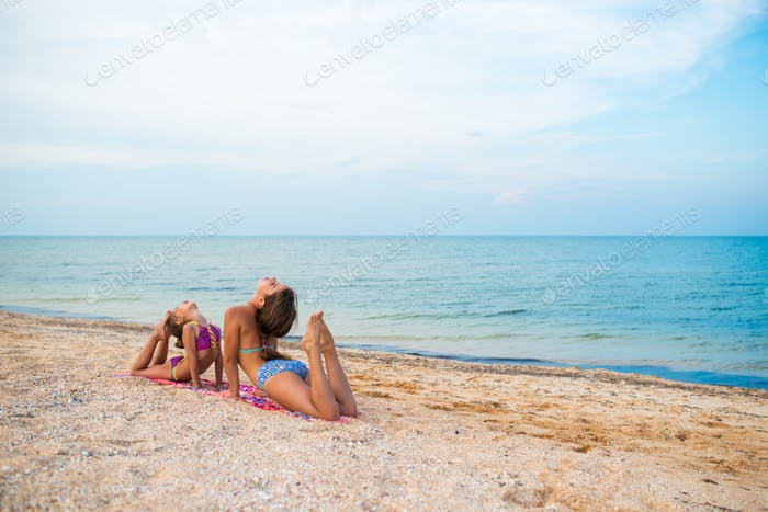 Charmante kleine Mädchen machen gymnastische Übungen auf Seesand