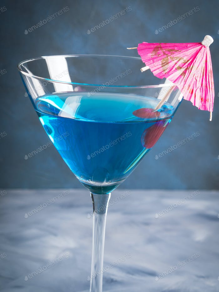 Blue cocktail in martini glass with umbrella