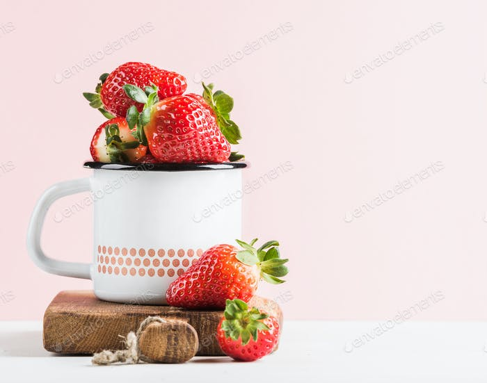 Fresh ripe red strawberries in country style enamel mug on rustic wooden board