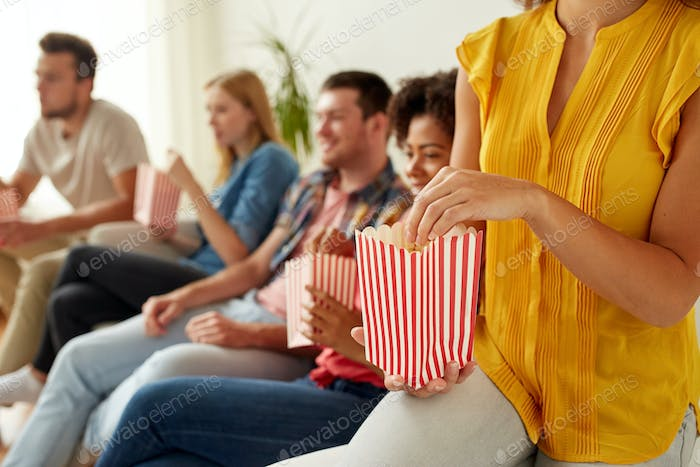 close up of happy friends eating popcorn at home