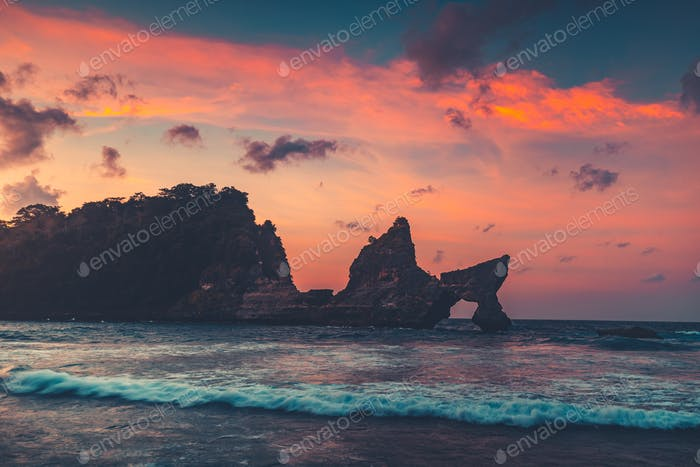 Beautiful Natural Rock Arch in Sunset Ocean Water