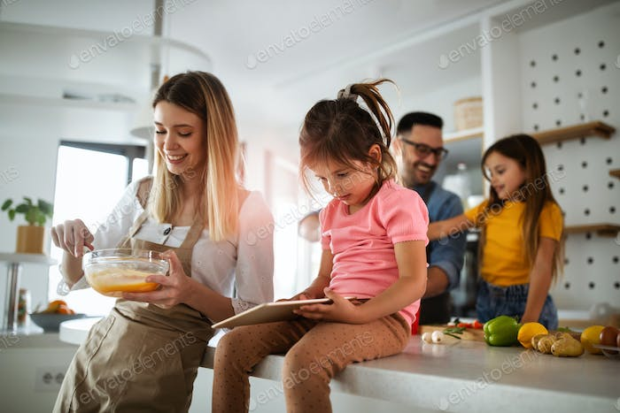 Overjoyed young family with kids having fun, cooking at home together