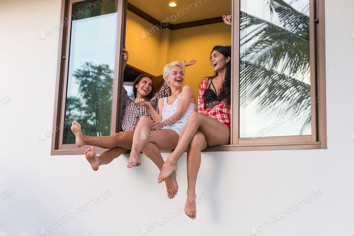 Young Girls Group Sitting On Window Sill Talking, Beautiful Woman Friends Communication