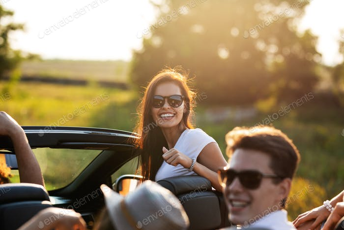 Gorgeous young dark-haired young woman in sunglasses is smiling and sitting with friends in a black
