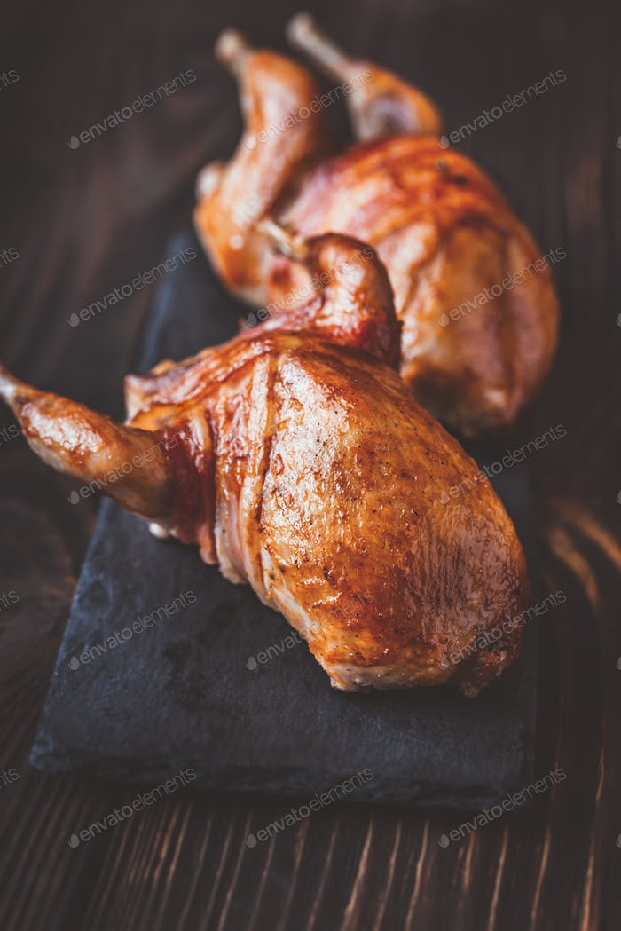 Two baked quails wrapped in bacon on the black stone board