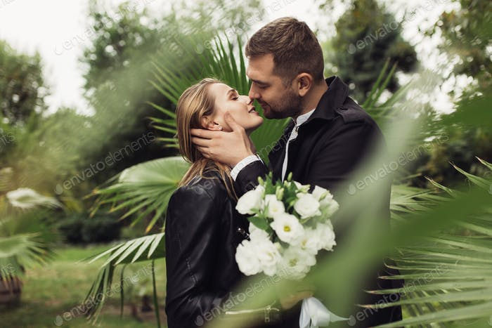 Young attractive man in trench coat happily kissing beautiful sm