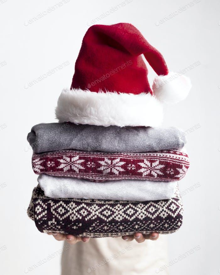 Woman giving Pile of sweaters with Christmas creative patterns