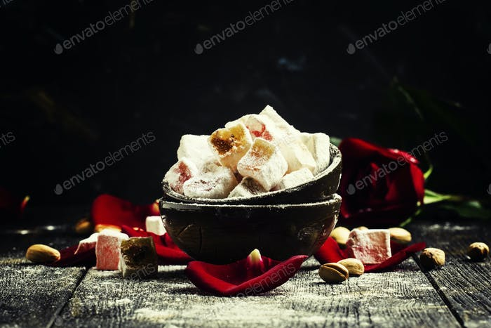 Rahat lukum, oriental sweets with pistachios and rose petals, low key, selective focus