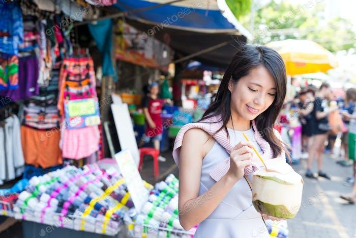 Woman enjoy coconut juicy at street market