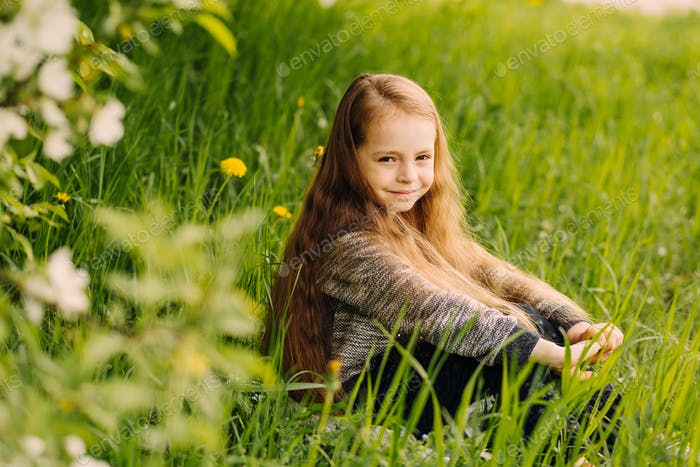 Portrait of little cute beautiful girl in garden