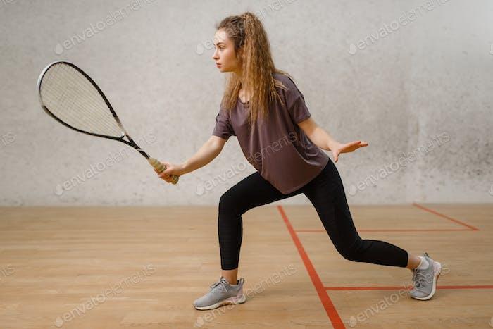 Weibliche Spieler mit Squashschläger in Aktion