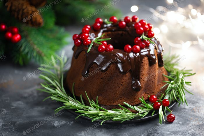 Christmas chocolate bundt cake with glaze decorated with fresh berries and rosemary