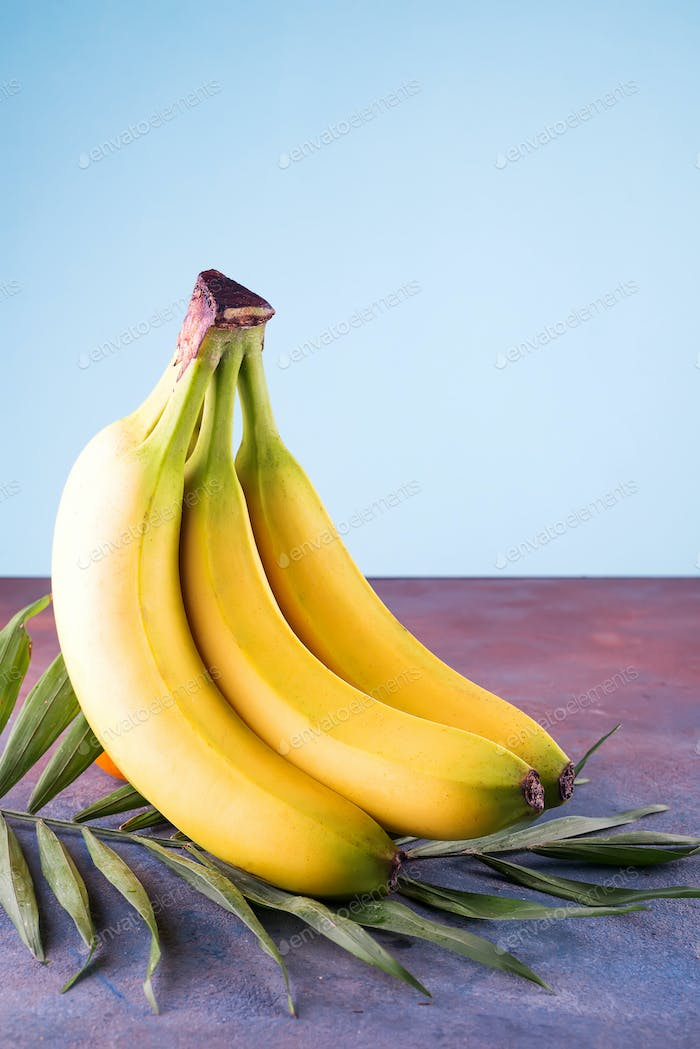 Bunch of bananas with palm leaf on stone background with copy space