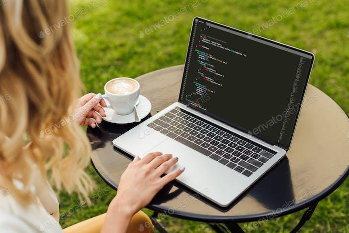imagen recortada de mujer usando laptop con código html en la mesa en el jardín