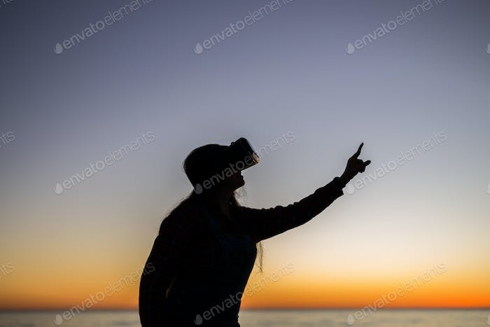 Young woman wearing virtual reality goggles on sky background dreams come true