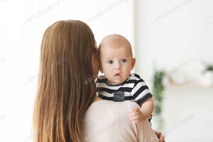 Niedliches kleines Baby auf der Schulter der Mutter liegend