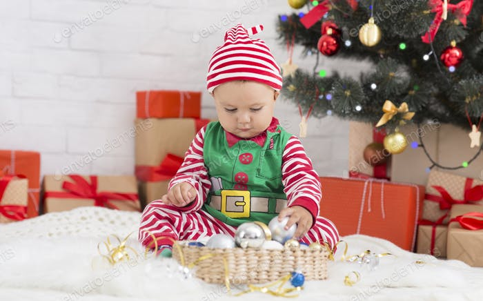 Cute baby elf playing with Xmas decorations