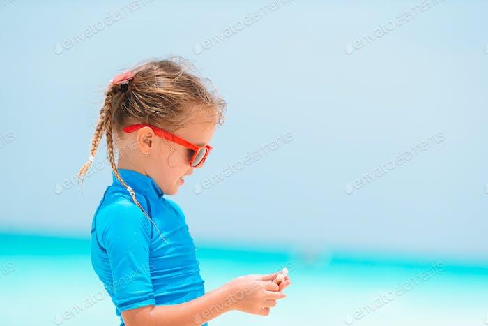 Adorable little girl playing with seashells on beach