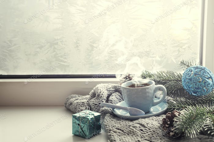 the window with a cup of hot drink