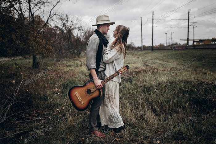 Musician with guitar and indie style woman in white sweater posing