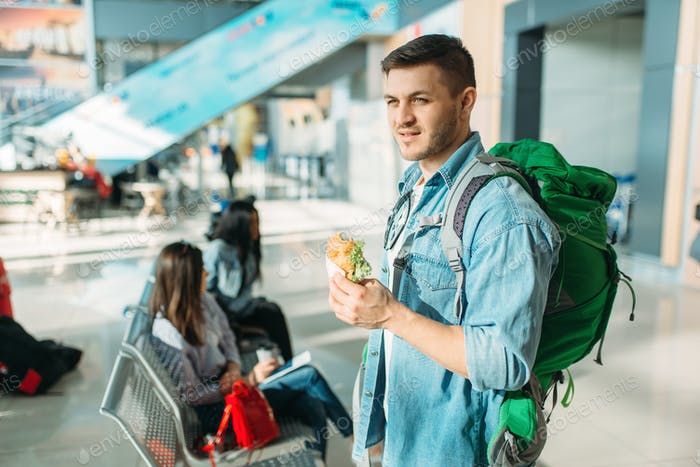Male tourist with backpack holds burger, airport