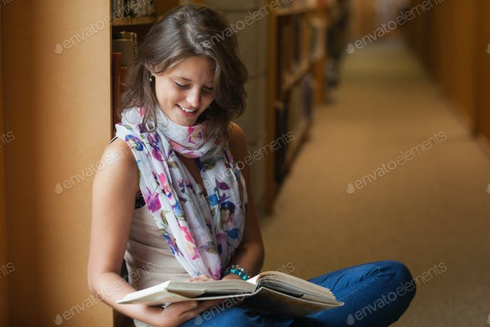 Side view of a female student sitting and reading a book in the library aisle