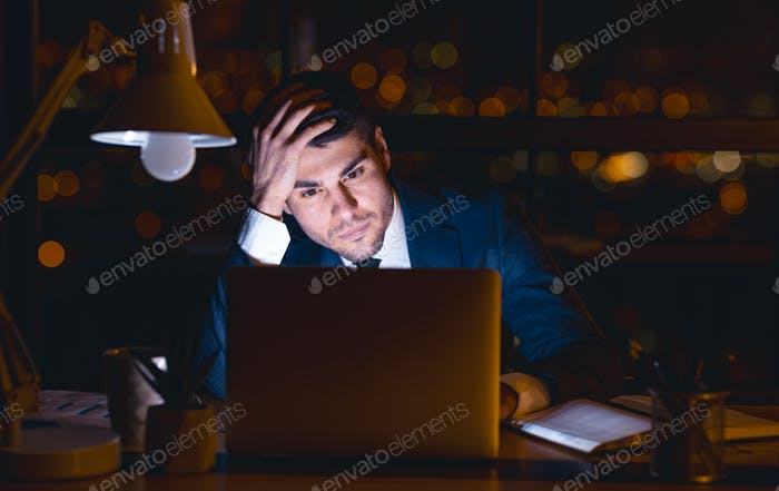 Entrepreneur At Laptop Thinking Touching Head Sitting Overnight In Office