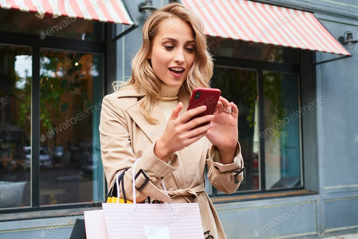 Surprised blond girl in stylish trench coat with shopping bags happily using cellphone on street
