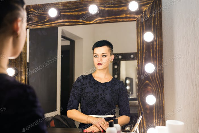Young woman with short hair looking herself reflection in mirror