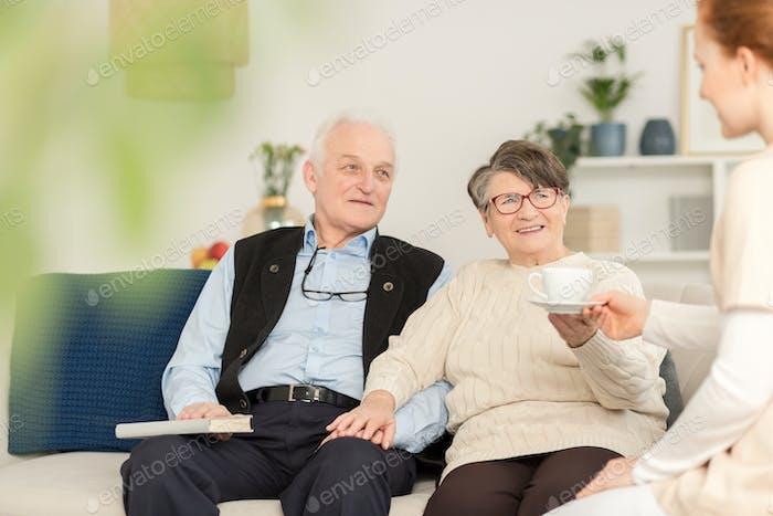 Friendly caregiver and senior couple