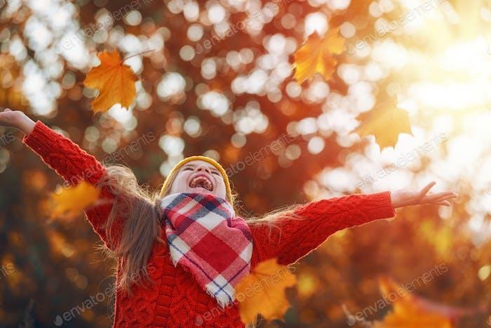 Kind spielen mit Herbstlaub