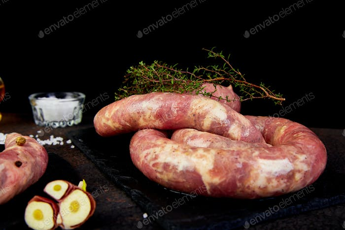 Raw spiral pork sausages with rosemary, salt and peper