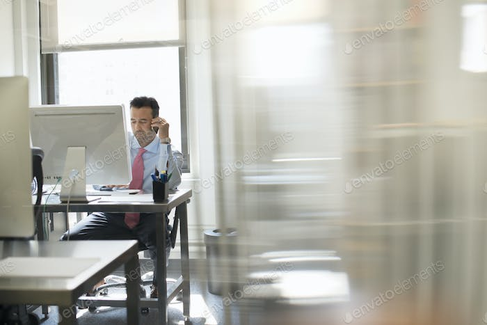 A man seated at a computer screen working on his own.