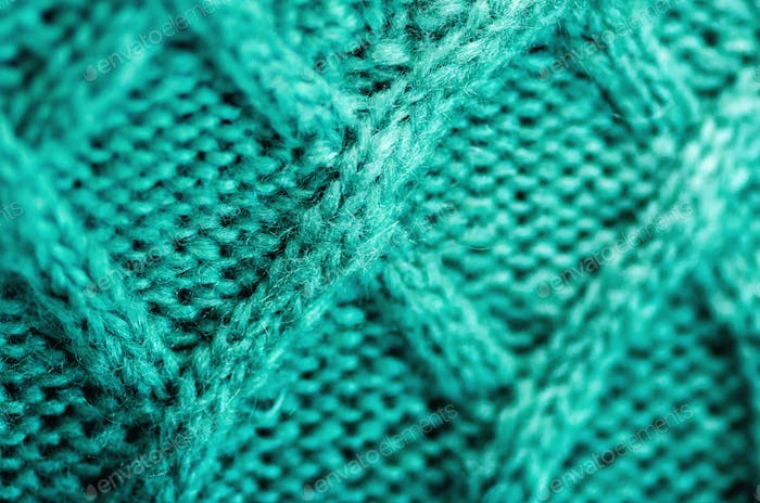 Knitted texture. Pattern fabric made of wool. Turquoise background, copy space