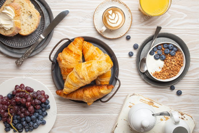 morning breakfast with fresh croissants, granola with yoghurt and berries, toasts, coffee
