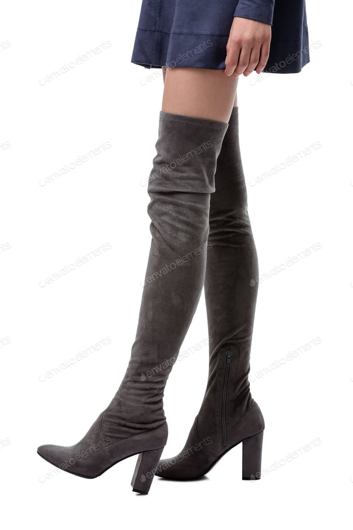 Close up photo of long woman legs in gray boots with heels on white background
