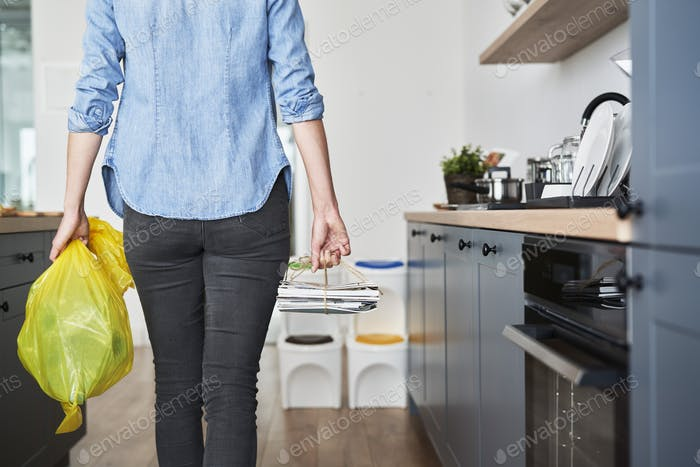 Woman going to bin with segregated paper and plastic