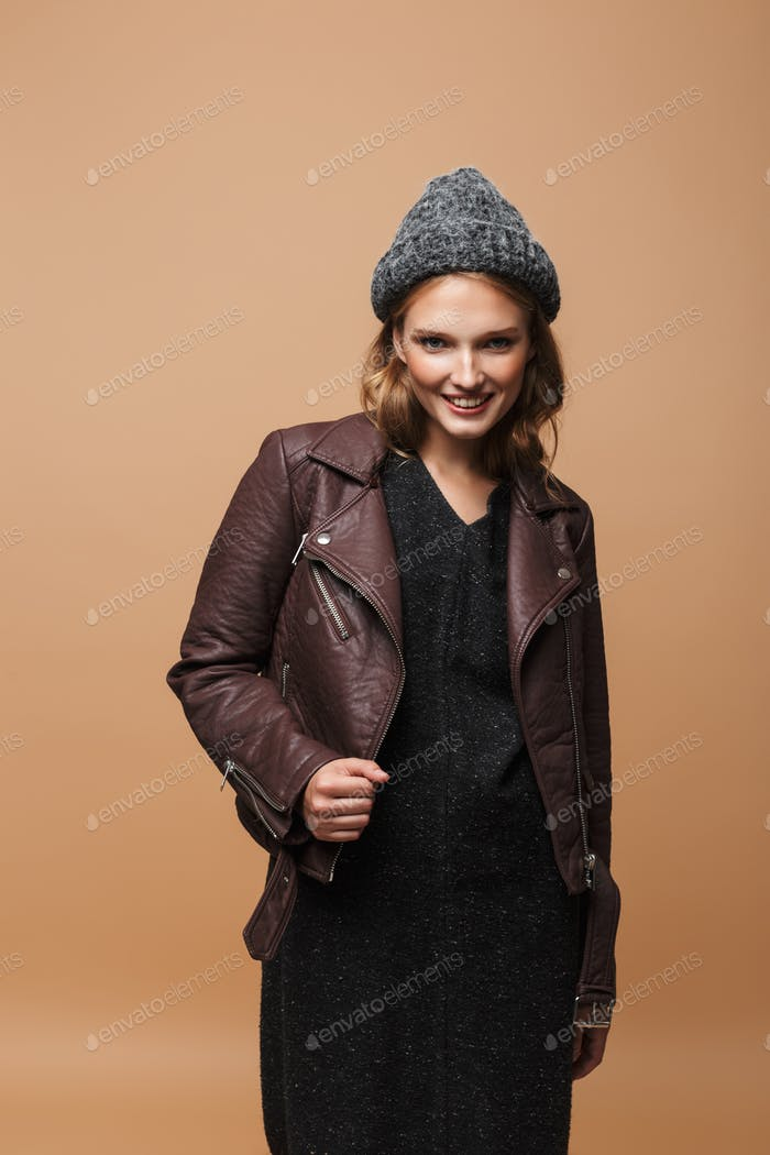Young beautiful joyful woman in hat, leather jacket and black dress happily looking in camera