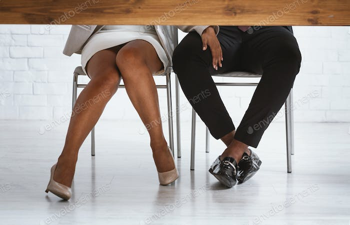 Closeup of black lady boss sexually molesting her male subordinate, touching his leg under table in