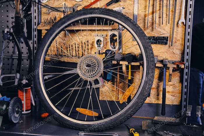 Bike wheel over service tool stand in a workshop.