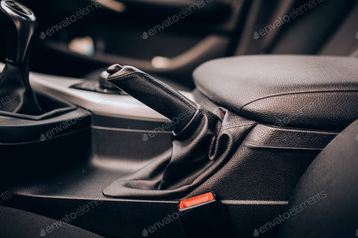 Interior modern car details - close up leather handbreak lever