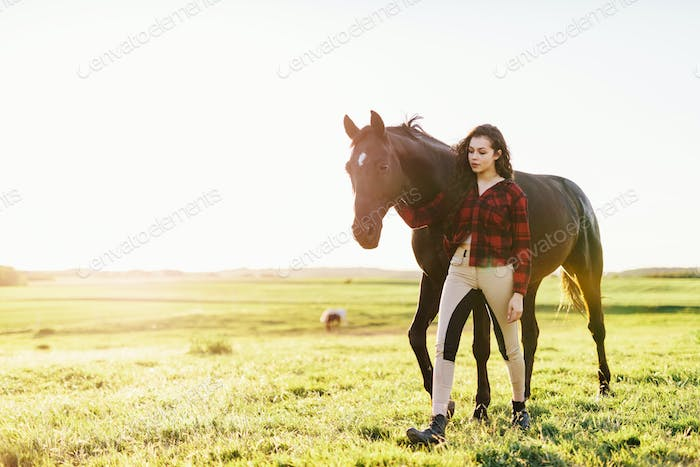 Young woman standing next to her black horse