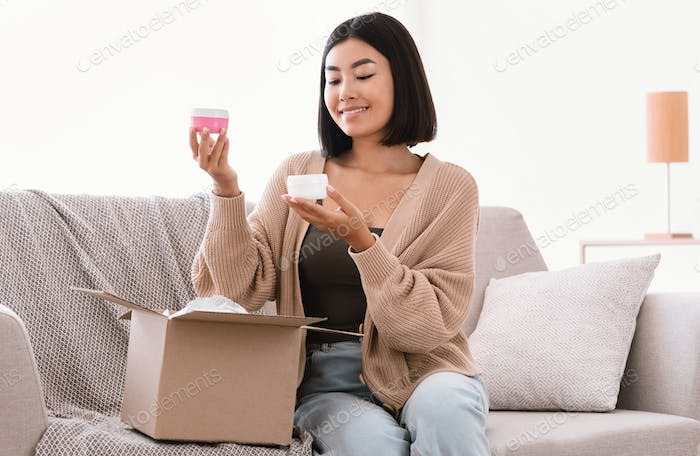 Happy asian woman unpacking parcel with beauty box