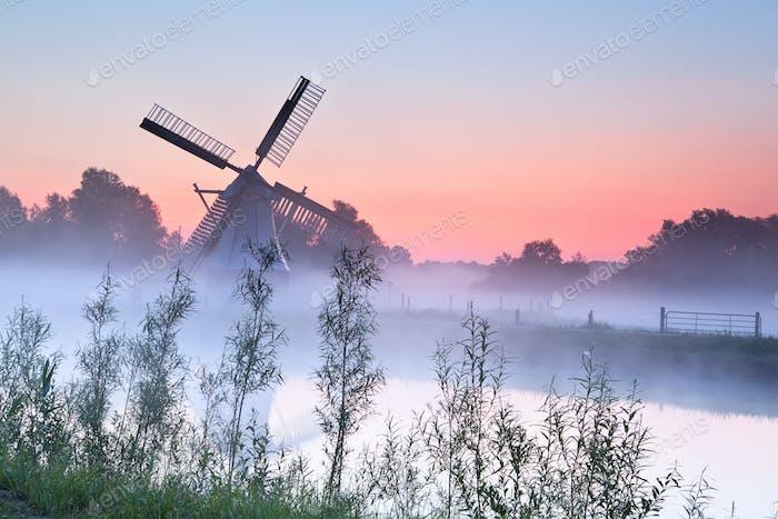 encantador molino de viento holandés al Amanecer