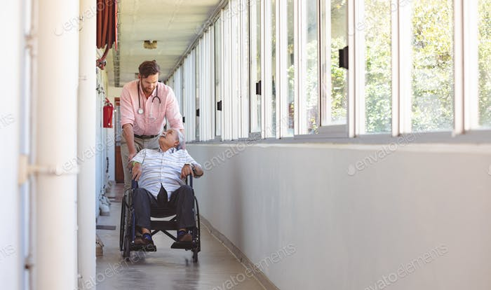 male doctor and senior man talking with each other while Caucasian doctor pushing his wheelchair