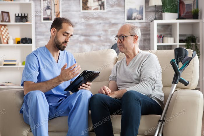 Young doctor in nursing home checking elderly age man treatment