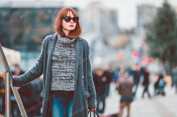 Styled woman in coat walking down the street
