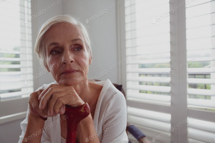 Thoughtful active senior Caucasian woman leaning on walking cane and looking away